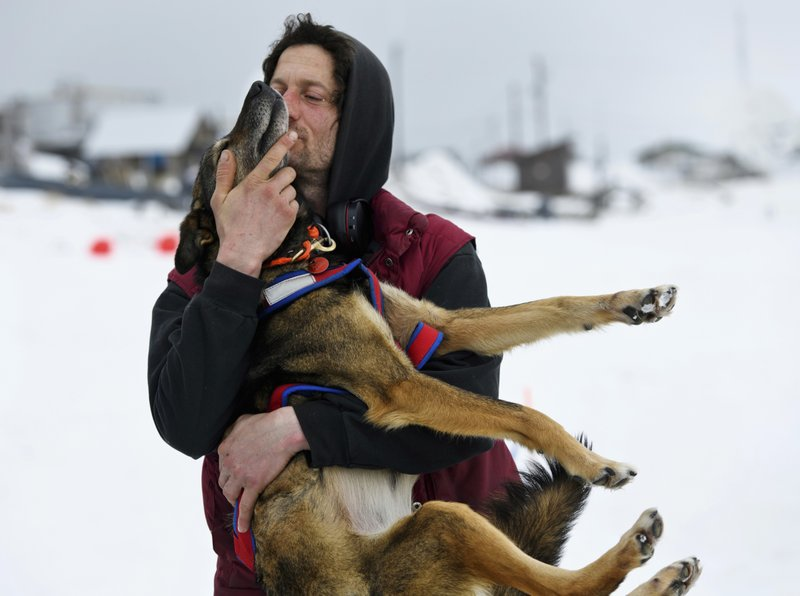 FILE - In this Sunday, March 10, 2019 file photo, Iditarod musher Nicolas Petit hugs one of his dogs before they leave Unalakleet, Alaska, during the Iditarod Trail Sled Dog Race. (Marc Lester/Anchorage Daily News via AP, File)