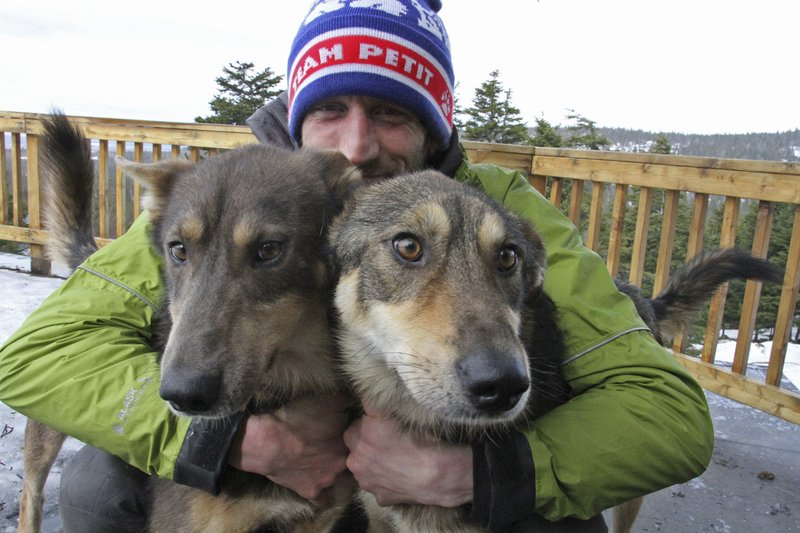 This Wednesday, March 20, 2019, photo shows Iditarod musher Nicolas Petit posing with two of his dogs in Anchorage, Alaska. (AP Photo/Mark Thiessen)