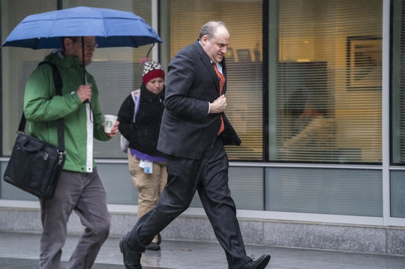 Andrew D. Goldstein, a lead prosecutor for special counsel Robert Mueller, dashes through the rain outside the building where the Mueller team is expected to soon conclude its investigation into Russian election meddling, possible collusion with Donald Trump's campaign officials and possible obstruction of justice by Trump, in Washington, Thursday, March 21, 2019. (AP Photo/J. Scott Applewhite)
