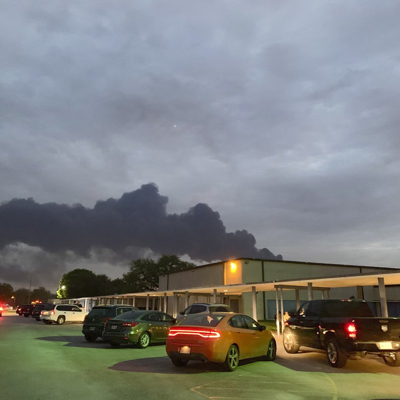 In this Tuesday, March 19, 2019 photo, shows smoke rising from a fire at the Intercontinental Terminals Company near the Carpenter Elementary School in Deer Park, Texas. (Jeffrey Fountain via AP)