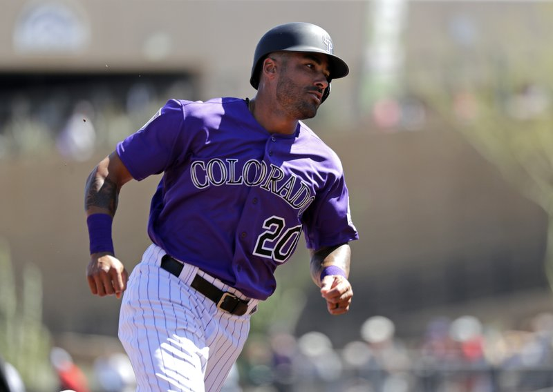 Colorado Rockies' Ian Desmond rounds third on his way to scoring against the Cincinnati Reds in the third inning of a spring training baseball game Monday, March 18, 2019, in Scottsdale, Ariz. (AP Photo/Elaine Thompson)