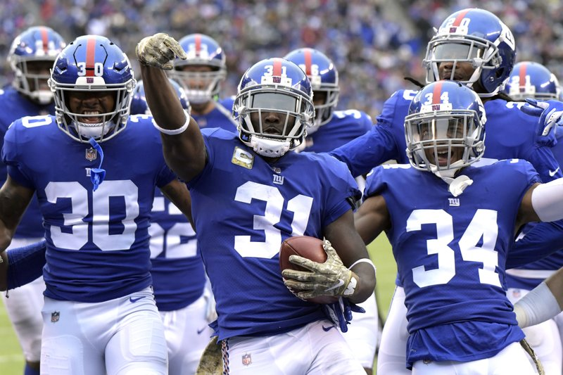 FILE - In this Nov. 18, 2018, file photo, New York Giants' Michael Thomas, center, celebrates an interception with his teammates during the first half of an NFL football game against the Tampa Bay Buccaneers in East Rutherford, N. (AP Photo/Bill Kostroun, File)