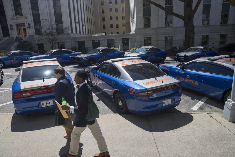 A line of Georgia State Trooper vehicles sit outside of the Georgia State Capitol building as members of the Senate debate HB 481 on the 35th legislative day at the Georgia State Capitol building in downtown Atlanta, Friday, March 22, 2019. (Alyssa Pointer/Atlanta Journal-Constitution via AP)