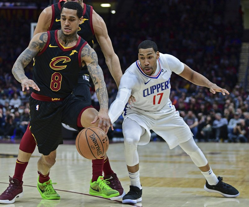 Los Angeles Clippers' Garrett Temple, right, kicks the ball away from Cleveland Cavaliers' Jordan Clarkson in the first half of an NBA basketball game, Friday, March 22, 2019, in Cleveland. (AP Photo/David Dermer)