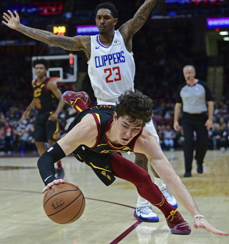 Cleveland Cavaliers' Cedi Osman falls to the floor after being fouled by Los Angeles Clippers' Lou Williams (23) in the first half of an NBA basketball game, Friday, March 22, 2019, in Cleveland. (AP Photo/David Dermer)