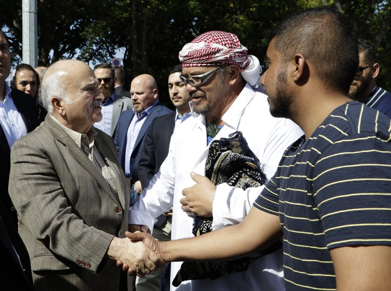 His Royal Highness Prince El Hassan bin Talal Hashemite, left, of the Kingdom of Jordan greets worshippers outside the Al Noor mosque in Christchurch, New Zealand, Saturday, March 23, 2019. (AP Photo/Mark Baker)