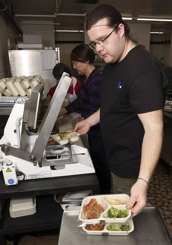In this Friday, March 15, 2019  photo, Aaron Pritzl, a cook for the Aging & Disability Resource Center of Eau Claire County's nutrition program, seals meals in the kitchen of the former Fall Creek (Wis. (Steve Kinderman/The Eau Claire Leader-Telegram via AP)