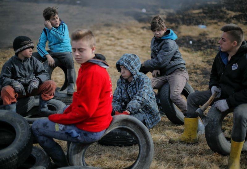In this photo taken on Sunday, March 10, 2019, a children sit on tires during a ritual marking the upcoming Clean Monday, the beginning of the Great Lent, 40 days ahead of Orthodox Easter, on the hills surrounding the village of Poplaca, in central Romania's Transylvania region. (AP Photo/Vadim Ghirda)