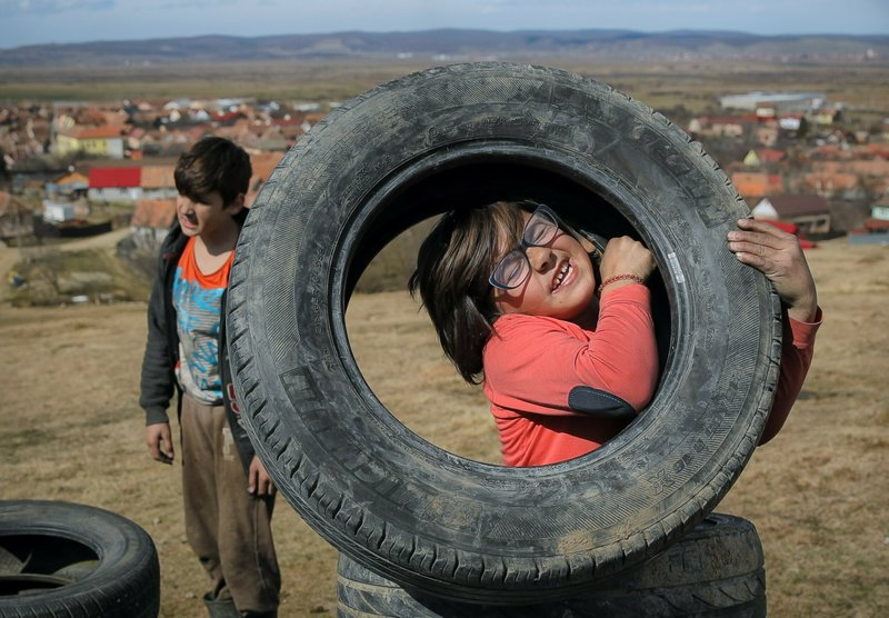 In this photo taken on Sunday, March 10, 2019, a little girl struggles to lift a tire during a ritual marking the upcoming Clean Monday, the beginning of the Great Lent, 40 days ahead of Orthodox Easter, on the hills surrounding the village of Poplaca, in central Romania's Transylvania region. (AP Photo/Vadim Ghirda)