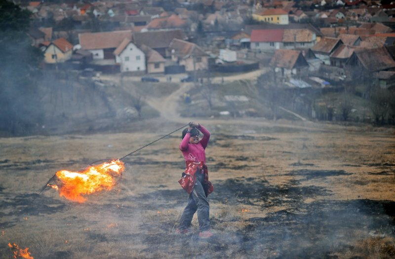 In this photo taken on Sunday, March 10, 2019, a little girl spins a burning tire on a metal chain during a ritual marking the upcoming Clean Monday, the beginning of the Great Lent, 40 days ahead of Orthodox Easter, on the hills surrounding the village of Poplaca, in central Romania's Transylvania region. (AP Photo/Vadim Ghirda)