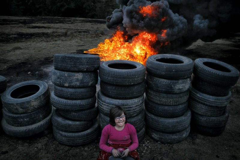 In this photo taken on Sunday, March 10, 2019, a little girl rests leaning against used tires during a ritual marking the upcoming Clean Monday, the beginning of the Great Lent, 40 days ahead of Orthodox Easter, on the hills surrounding the village of Poplaca, in central Romania's Transylvania region. (AP Photo/Vadim Ghirda)