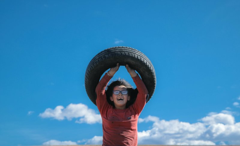 In this photo taken on Sunday, March 10, 2019, a little girl laughs lifting a tire before a ritual marking the upcoming Clean Monday, the beginning of the Great Lent, 40 days ahead of Orthodox Easter, on the hills surrounding the village of Poplaca, in central Romania's Transylvania region. (AP Photo/Vadim Ghirda)