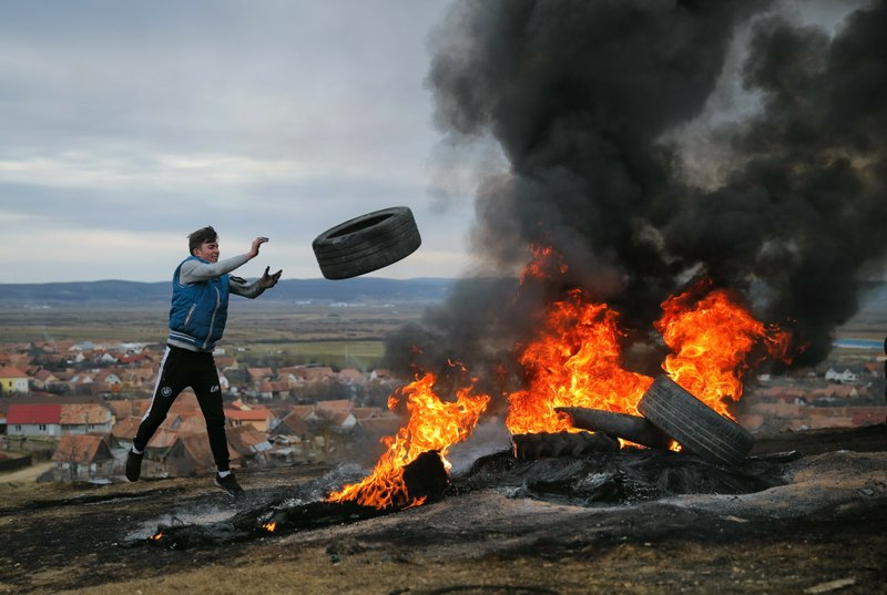 In this photo taken on Sunday, March 10, 2019, a young man throws a tire during a ritual marking the upcoming Clean Monday, the beginning of the Great Lent, 40 days ahead of Orthodox Easter, on the hills surrounding the village of Poplaca, in central Romania's Transylvania region. (AP Photo/Vadim Ghirda)