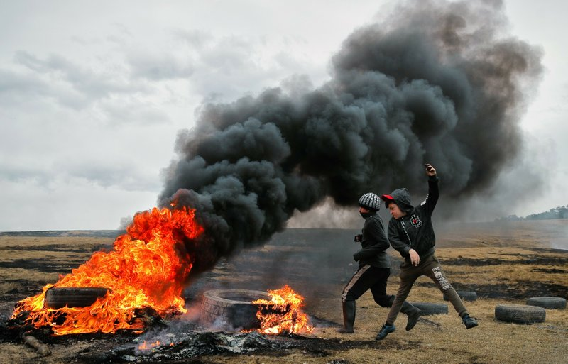 In this picture taken on Sunday, March 10, 2019, children jump after pushing a burning tire during a ritual marking the upcoming Clean Monday, the beginning of the Great Lent, 40 days ahead of Orthodox Easter, on the hills surrounding the village of Poplaca, in central Romania's Transylvania region. (AP Photo/Vadim Ghirda)
