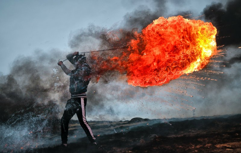 In this photo taken on Sunday, March 10, 2019, a young man spins a burning tire on a metal chain during a ritual marking the upcoming Clean Monday, the beginning of the Great Lent, 40 days ahead of Orthodox Easter, on the hills surrounding the village of Poplaca, in central Romania's Transylvania region. (AP Photo/Vadim Ghirda)
