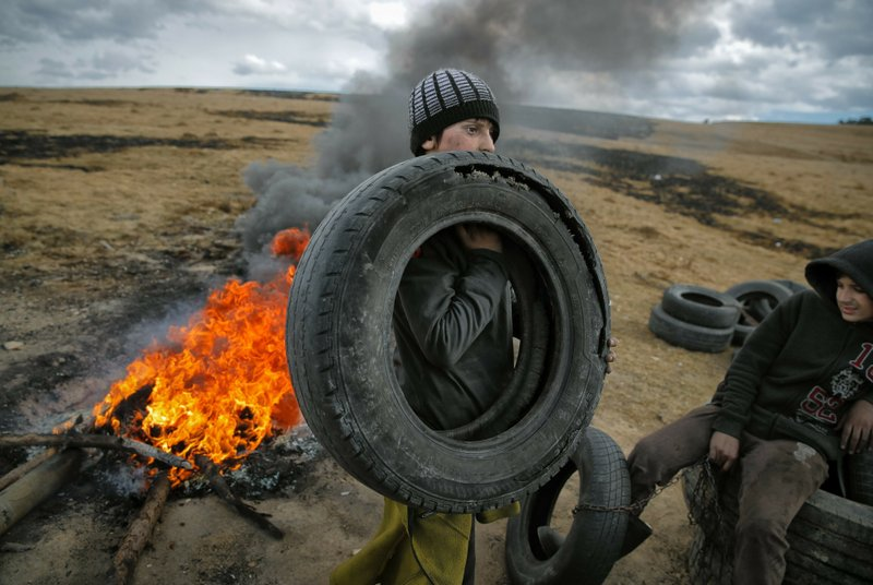 In this photo taken on Sunday, March 10, 2019, a boy holds a tire, during a ritual marking the upcoming Clean Monday, the beginning of the Great Lent, 40 days ahead of Orthodox Easter, on the hills surrounding the village of Poplaca, in central Romania's Transylvania region. (AP Photo/Vadim Ghirda)