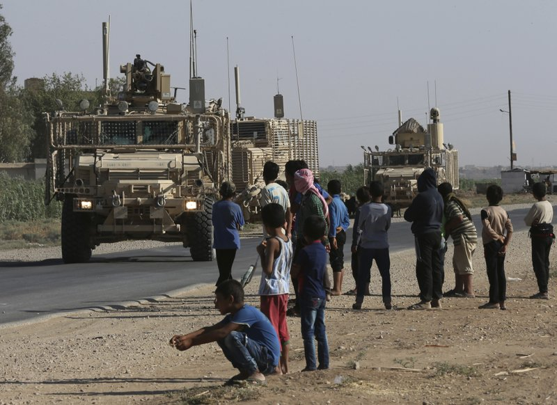 FILE - In this July 26, 2017, file photo, Syrians look at a U.S. armored vehicle convoy on a road that leads to Raqqa, northeast Syria. (AP Photo/Hussein Malla, File)