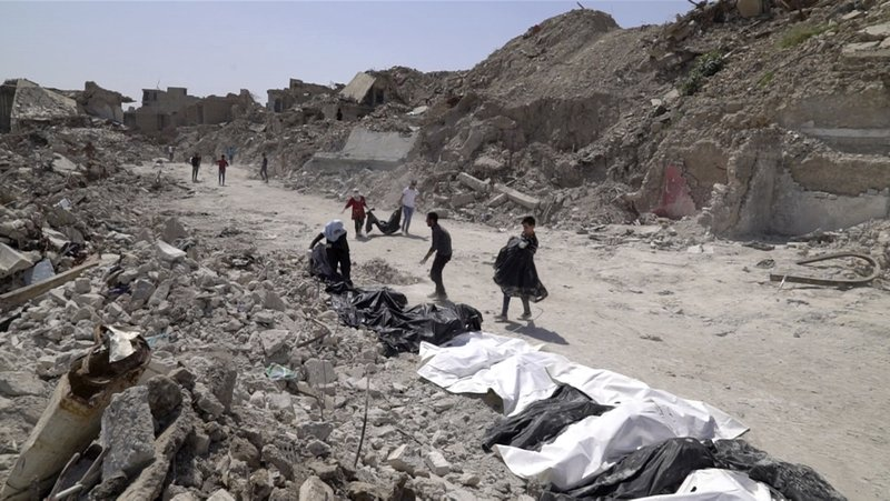 FILE - In this file image made from video taken on Monday, April 9, 2018, bodies are recovered by volunteers in Mosul's Old City. (AP Photo/Balint Szlanko, File)
