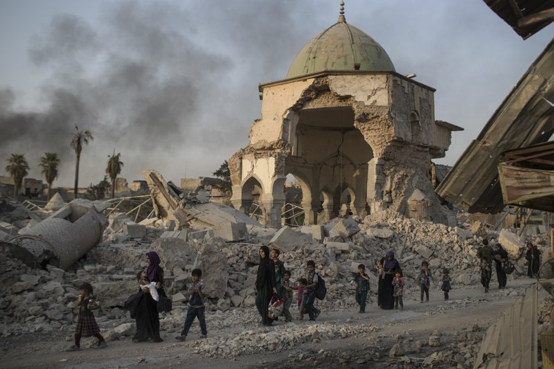 FILE - In this July 4, 2017, file photo, fleeing Iraqi civilians walk past the heavily damaged al-Nuri mosque as Iraqi forces continue their advance against Islamic State militants in Iraq's Old City of Mosul. (AP Photo/Felipe Dana, File)