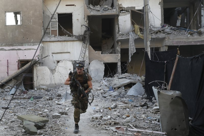 FILE - In this July 27, 2017, file photo, a U.S.-backed Syrian Democratic Forces fighter runs in front of a damaged building as he crosses a street on the front line, in Raqqa, Syria. (AP Photo/Hussein Malla, File)
