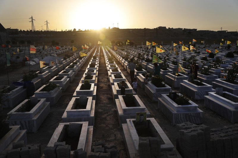 FILE - In this July 28, 2017, file photo, Kurdish citizens visit the graves of their relatives who were killed while fighting against Islamic State militants in Raqqa and other places, at a cemetery in Kobani, Syria. (AP Photo/Hussein Malla, File)