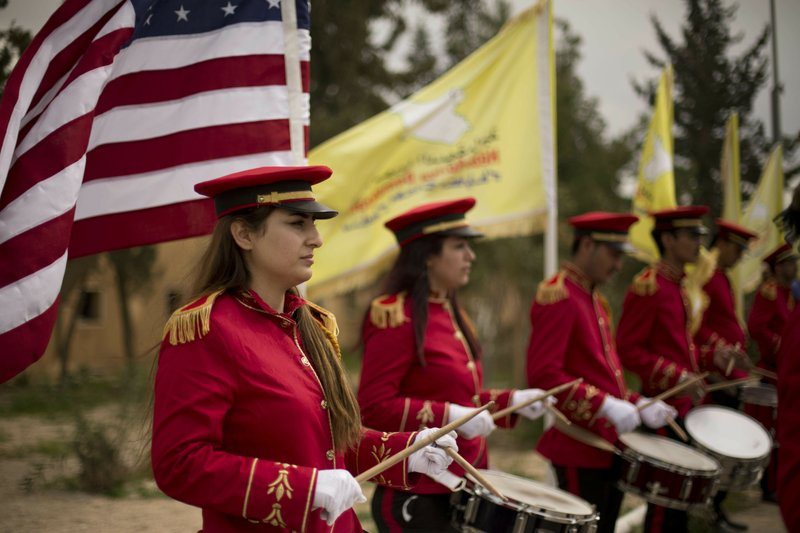 A military band performs ahead of a ceremony at al-Omar Oil Field marking the U.S.-backed Syrian Democratic Forces (SDF) capture of Baghouz, Syria, after months of fighting to oust Islamic State militants Saturday, March 23, 2019. (AP Photo/Maya Alleruzzo)