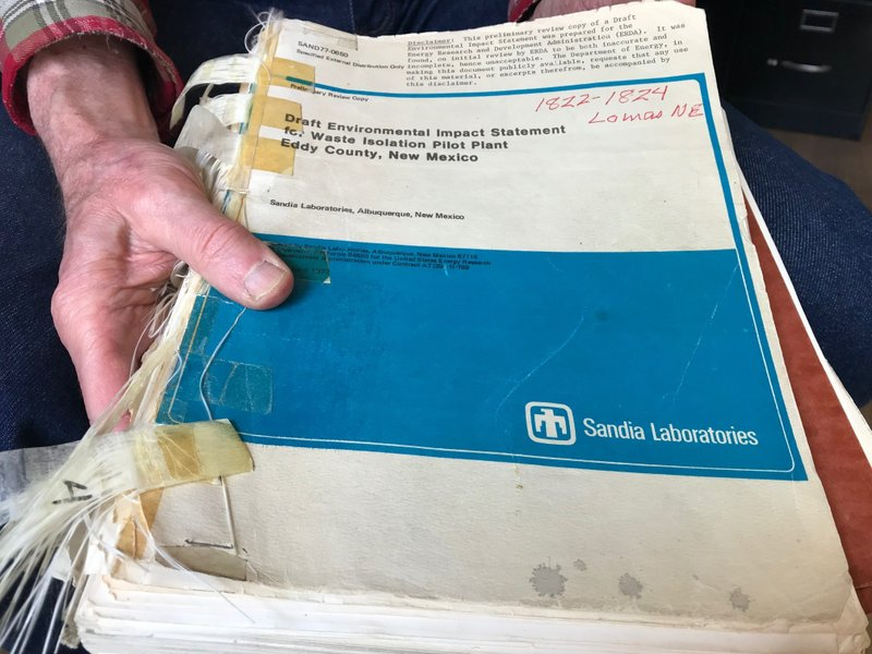 In this March 5, 2019 photo, Don Hancock of the Southwest Research and Information Center holds an early draft copy of an environmental review related to the Waste Isolation Pilot Plant that was planned for southern New Mexico. (AP Photo/Susan Montoya Bryan)