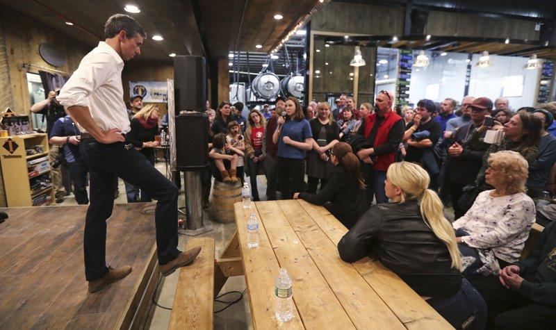 Former Texas congressman Beto O'Rourke rests his foot on a picnic table as he listens to a question during a campaign stop at a brewery in Conway, N. (AP Photo/Charles Krupa)
