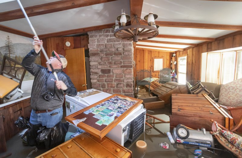 Steve O'Donnell works to open a skylight while standing in floodwaters inside a home Friday, March 22, 2019, in Bellevue, Neb. (Kent Sievers/Omaha World-Herald via AP)