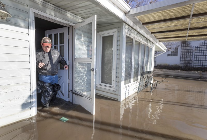 Steve O'Donnell exits his parent's flooded lake house in the Hanson's Lake area Friday, March 22, 2019, in Bellevue, Neb. (Kent Sievers/Omaha World-Herald via AP)