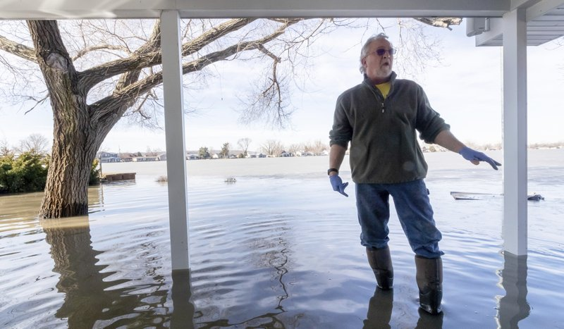 Tim Bazar stands on the back deck of his flooded house Friday, March 22, 2019, in Bellevue, Neb. Flooding in Nebraska has caused an estimated $1. (Kent Sievers-/Omaha World-Herald via AP)