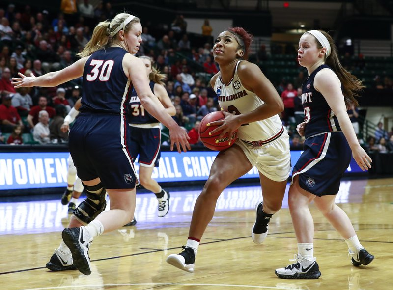 South Carolina guard Te'a Cooper, center, goes through Belmont defenders Ellie Harmeyer, left, and Darby Maggard, right, for a basket during a first-round game in the NCAA women's college basketball tournament in Charlotte, N. (AP Photo/Jason E. Miczek)