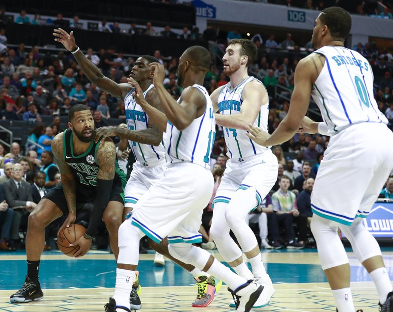 Boston Celtics forward Marcus Morris, left, is swarmed by the Charlotte Hornets defense in the first half of an NBA basketball game Saturday, March 23, 2019, in Charlotte, N. (AP Photo/Jason E. Miczek)