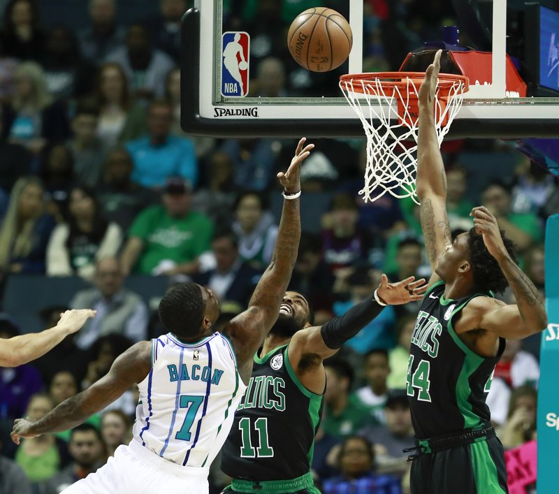 Charlotte Hornets guard Dwayne Bacon (7) reaches for a basket while being covered by Boston Celtics defenders Kyrie Irving (11) and Robert Williams (44) in the first half of an NBA basketball game Saturday, March 23, 2019, in Charlotte, N. (AP Photo/Jason E. Miczek)