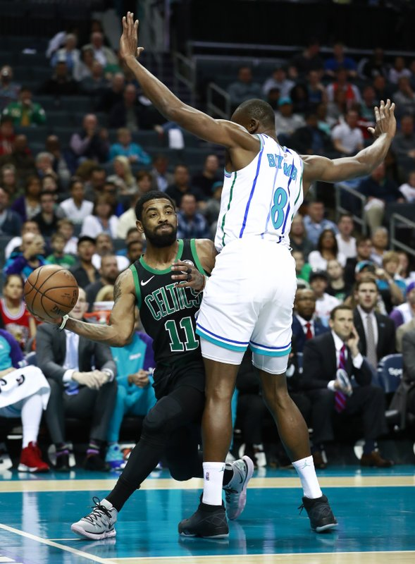 Boston Celtics guard Kyrie Irving (11) passes around Charlotte Hornets center Bismack Biyombo in the first half of an NBA basketball game Saturday, March 23, 2019, in Charlotte, N. (AP Photo/Jason E. Miczek)