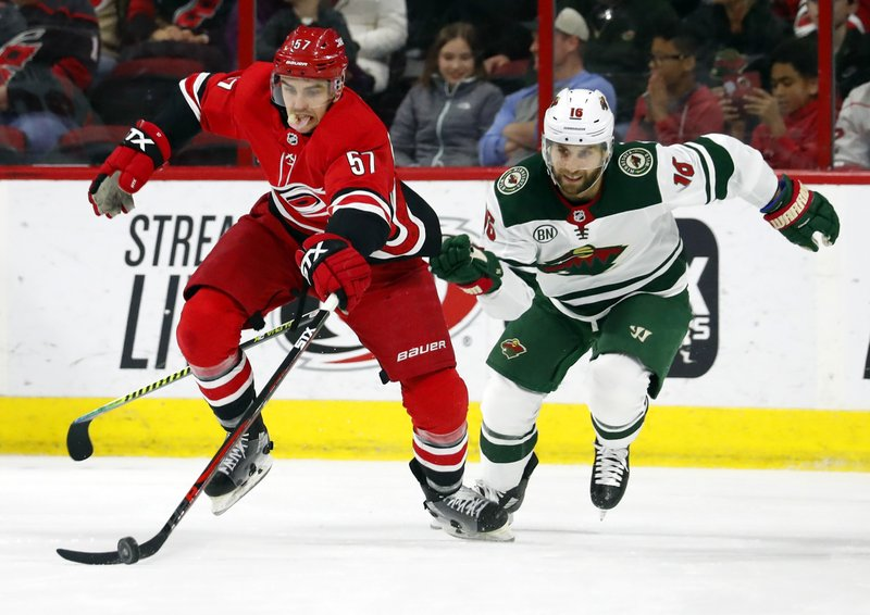 Carolina Hurricanes' Trevor van Riemsdyk (57) battles Minnesota Wild's Jason Zucker (16) for the puck during the second period of an NHL hockey game, Saturday, March 23, 2019, in Raleigh, N. (AP Photo/Karl B DeBlaker)