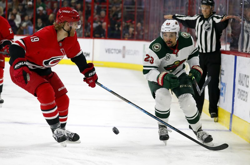 Minnesota Wild's J.T. Brown (23) chips the puck past Carolina Hurricanes' Dougie Hamilton (19) during the second period of an NHL hockey game, Saturday, March 23, 2019, in Raleigh, N. (AP Photo/Karl B DeBlaker)