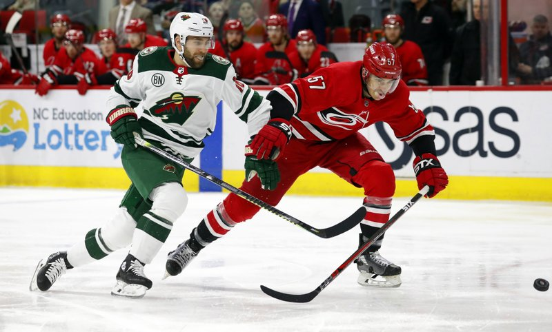 Minnesota Wild's Jason Zucker (16) chips the puck ahead of Carolina Hurricanes' Trevor van Riemsdyk (57) during the first period of an NHL hockey game, Saturday, March 23, 2019, in Raleigh, N. (AP Photo/Karl B DeBlaker)
