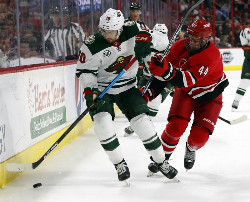 Minnesota Wild Matt Reid (10) tries to control the puck as he is checked by Carolina Hurricanes' Calvin de Haan (44) during the first period of an NHL hockey game, Saturday, March 23, 2019, in Raleigh, N. (AP Photo/Karl B DeBlaker)