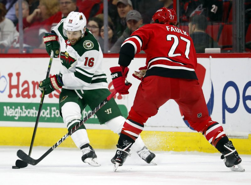 Minnesota Wild's Jason Zucker (16) battles Carolina Hurricanes' Justin Faulk (27) for the puck during the first period of an NHL hockey game, Saturday, March 23, 2019, in Raleigh, N. (AP Photo/Karl B DeBlaker)