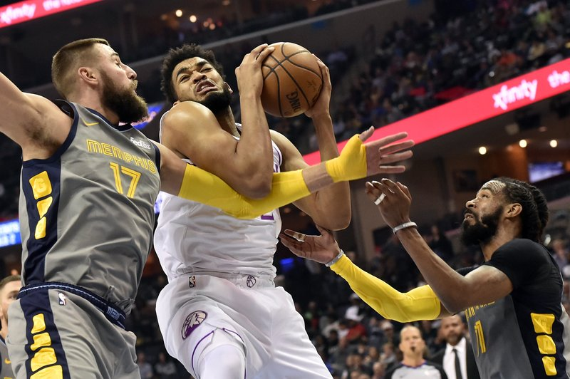 Minnesota Timberwolves center Karl-Anthony Towns, center, struggles for control of the ball against Memphis Grizzlies center Jonas Valanciunas (17) and guard Mike Conley, right, in the second half of an NBA basketball game Saturday, March 23, 2019, in Memphis, Tenn. (AP Photo/Brandon Dill)