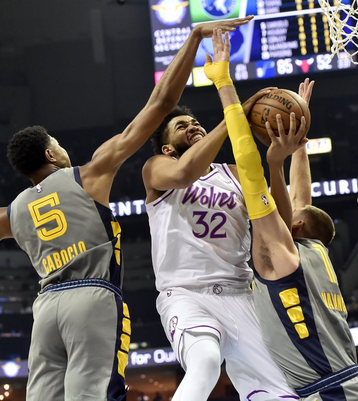 Minnesota Timberwolves center Karl-Anthony Towns (32) shoots against Memphis Grizzlies center Jonas Valanciunas, right, and forward Bruno Caboclo (5) in the second half of an NBA basketball game Saturday, March 23, 2019, in Memphis, Tenn. (AP Photo/Brandon Dill)