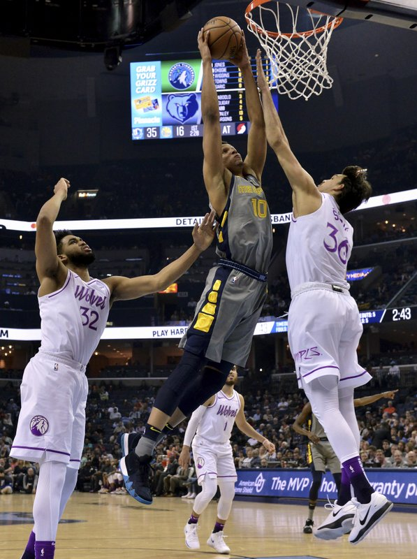 Memphis Grizzlies forward Ivan Rabb (10) goes up for a dunk between Minnesota Timberwolves forward Dario Saric (36) and center Karl-Anthony Towns (32) in the first half of an NBA basketball game Saturday, March 23, 2019, in Memphis, Tenn. (AP Photo/Brandon Dill)