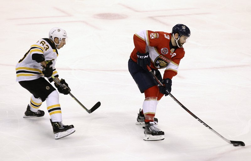 Florida Panthers' Keith Yandle (3) moves the puck as Boston Bruins' Brad Marchand, left, defends during the third period of an NHL hockey game, Saturday, March 23, 2019, in Sunrise, Fla. (AP Photo/Luis M. Alvarez)