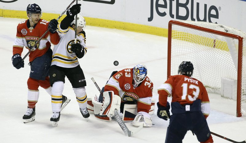Boston Bruins' Karson Kuhlman, second from left, looks for the puck as Florida Panthers goalkeeper Sam Montembeault (33), Mike Matheson, left, and Mark Pysyk (13) defend during the first period of an NHL hockey game, Saturday, March 23, 2019, in Sunrise, Fla. (AP Photo/Luis M. Alvarez)