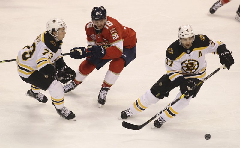 Boston Bruins' Patrice Bergeron, right, moves the puck with Charlie McAvoy (73) as Florida Panthers' Aleksander Barkov (16) defends during the first period of an NHL hockey game, Saturday, March 23, 2019, in Sunrise, Fla. (AP Photo/Luis M. Alvarez)