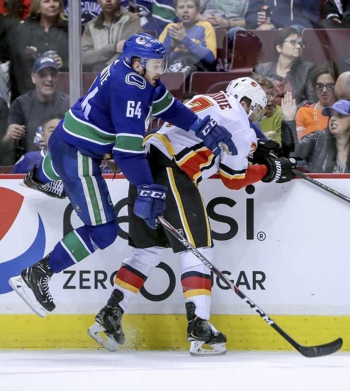 Calgary Flames' TJ Brodie (7) checks Vancouver Canucks' Tyler Motte (64) during the second period of an NHL hockey game Saturday, March 23, 2019, in Vancouver, British Columbia. (Ben Nelms/The Canadian Press via AP)