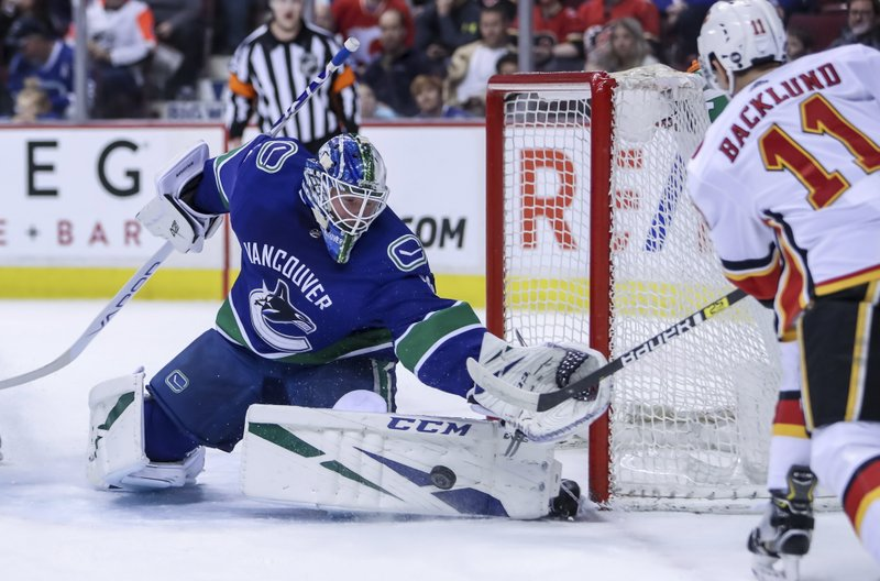 Vancouver Canucks goaltender Jacob Markstrom (25) makes a save against Calgary Flames' Mikael Backlund (11) during the first period of an NHL hockey game Saturday, March 23, 2019, in Vancouver, British Columbia. (Ben Nelms/The Canadian Press via AP)