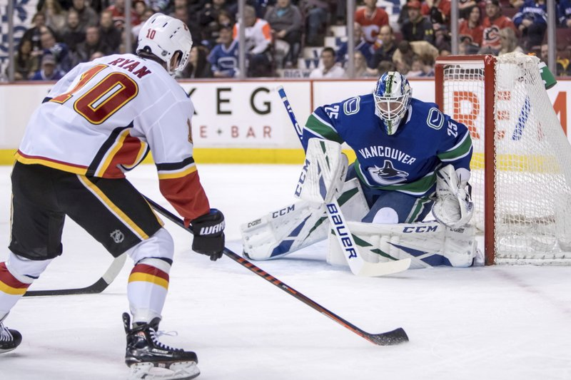 Vancouver Canucks goaltender Jacob markstrom (25) makes a save against Calgary Flames' Derek Ryan (10) during the first period of an NHL hockey game Saturday, March 23, 2019, in Vancouver, British Columbia. (Ben Nelms/The Canadian Press via AP)