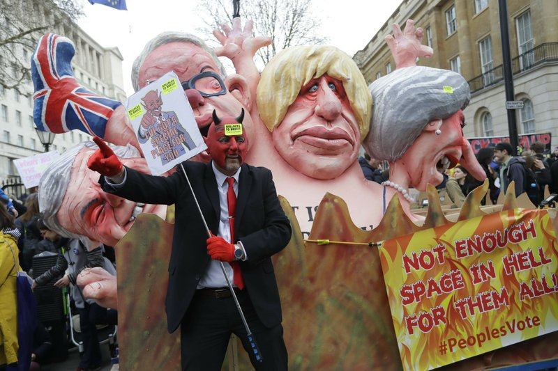 Effigies of British Prime Minister Theresa May and Conservative politicians Boris Johnson and Michael Gove, from right, and displayed during a Peoples Vote anti-Brexit march in London, Saturday, March 23, 2019. (AP Photo/Kirsty Wigglesworth)